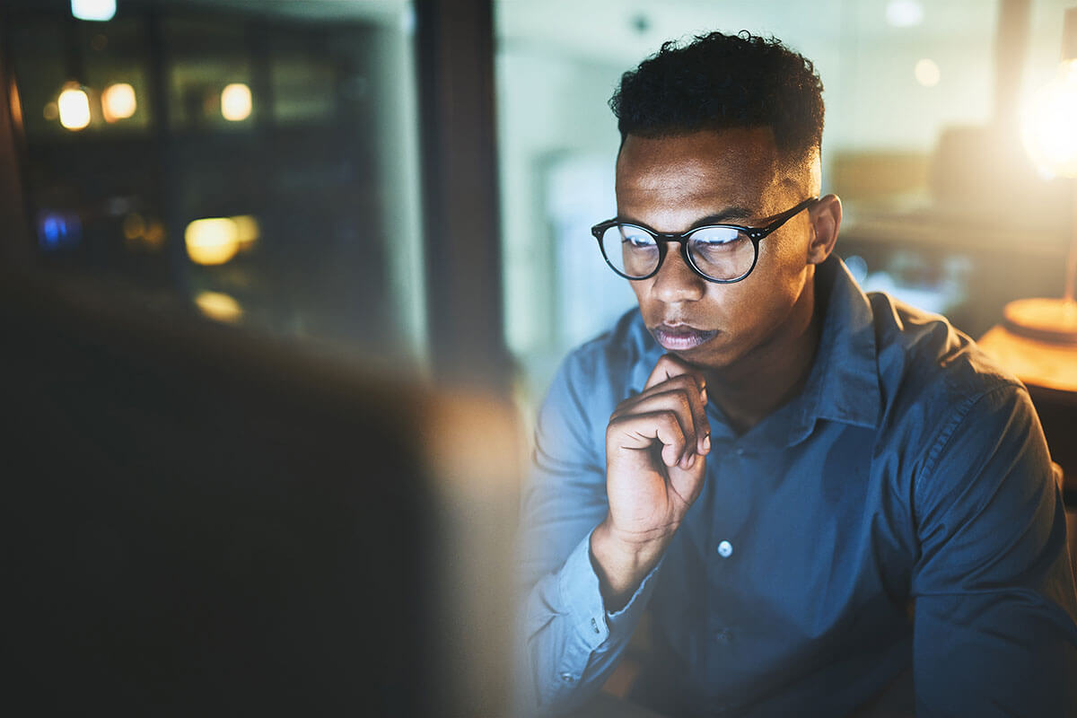 Male office worker with glasses looking pensive at monitor.