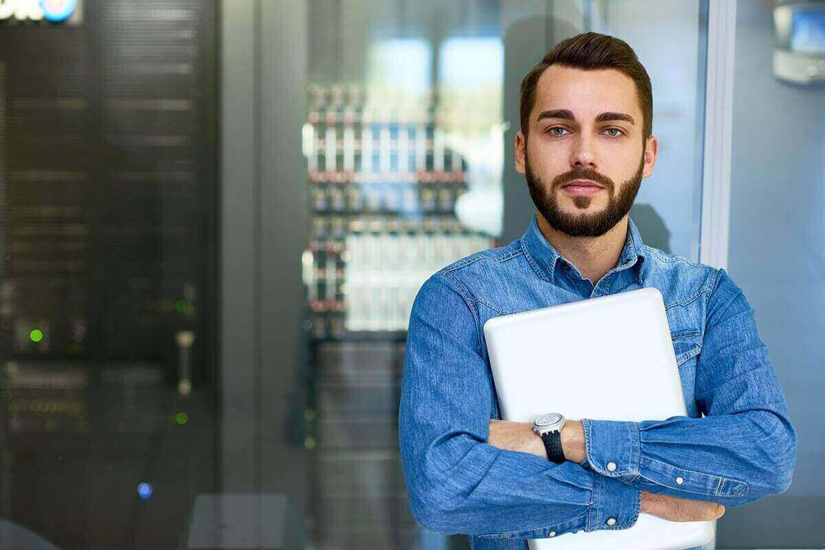 Male office worker standing in front of equipment holding laptop.