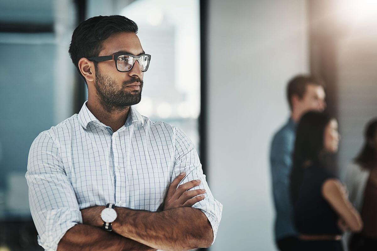 Office worker with glasses standing with arm crossed to the side of colleagues.