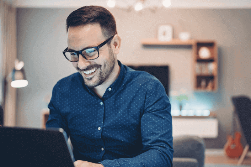 Home worker with glasses smiling and working on laptop