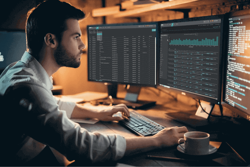 Cysiv Data Engineer viewing dashboards on multiple monitors.